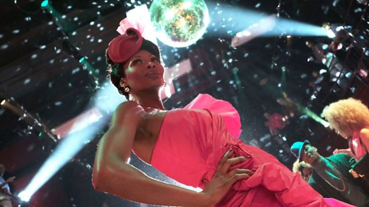 The character Elektra Abundance, in a bright red gown and hat, stands under a disco ball.