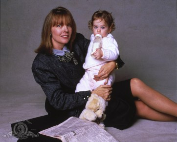 Diane Keaton sits on the floor in a skirt suit, holding a baby, her briefcase and newspaper on the floor next to her