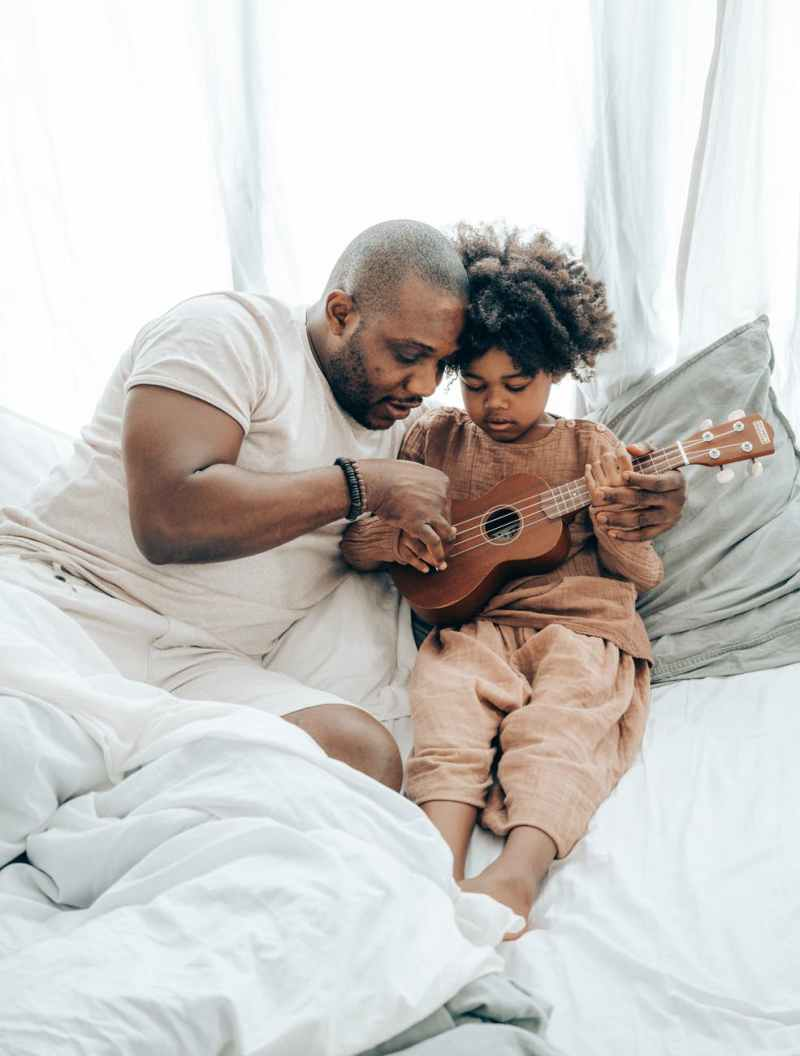 ethnic father teaching kid playing on ukulele at home