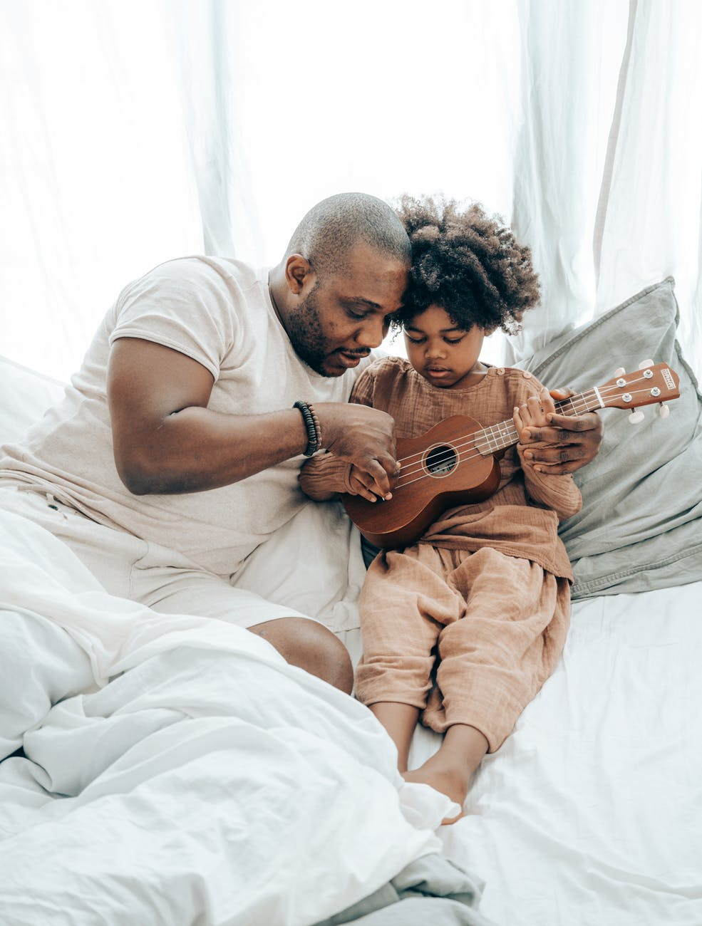ethnic father teaching kid playing on ukulele at home