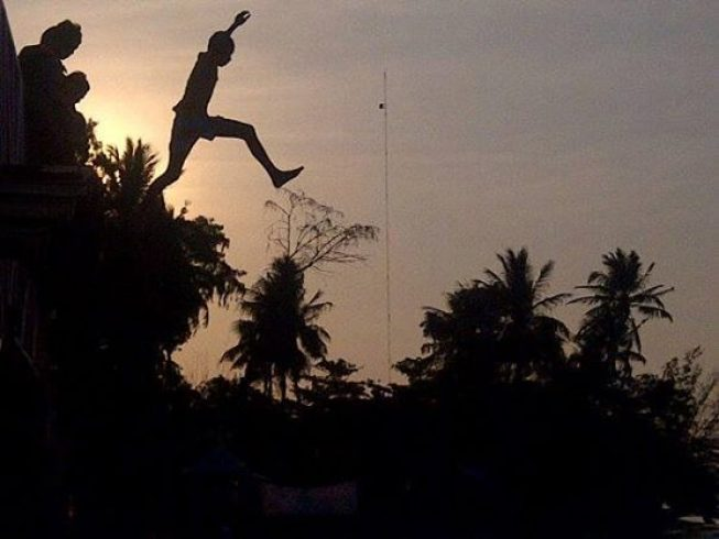 """Senja di Pulau Tidung, Kabupaten Kepulauan Seribu. Anak pulau meloncat dari atas """"Jembatan Cinta"""" (foto : Nur Terbit)"""