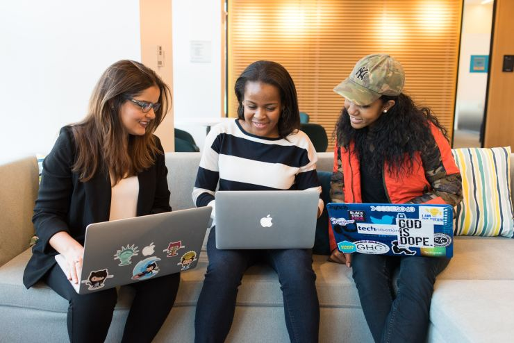 This is a picture of 2 African American women and 1 caucasian woman sitting together and looking at their laptops together.  It is representing how counseling available at Nurtured Well, LLC in Towson , Maryland and on-line throughout Maryland.