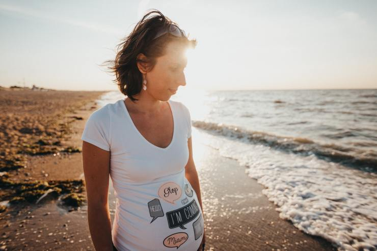 This is a picture of a pregnant woman looking pensive while standing on a beach.  She is considering taking medication while pregnant.  At Nurtured Well in Towson, MD we can help women make theses decisions.