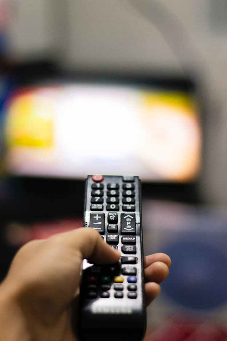 person holding black remote control. This represents vegging out to TV because you are not present.