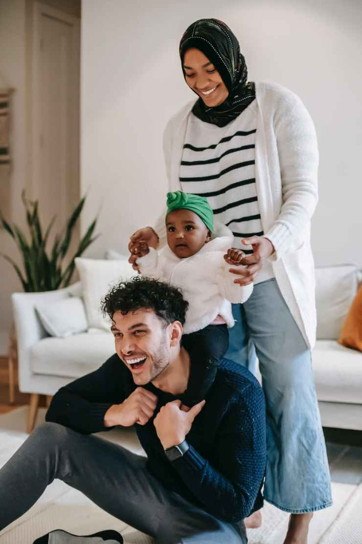cheerful diverse family with toddler daughter having fun at home.  Mom and dad are using mindfulness practice to enjoy their time with their family.