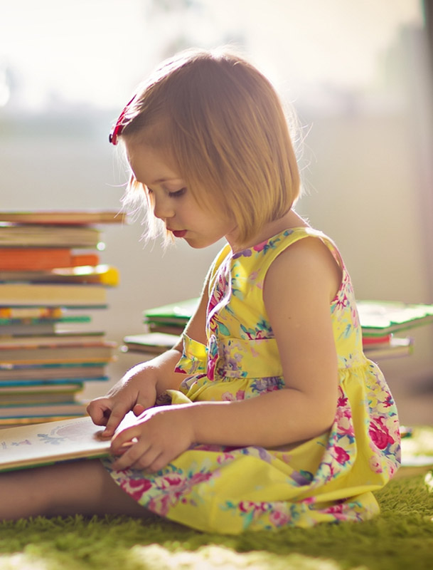 little-girl-in-a-yellow-dress-reading-a-book-sitting-on-the-floor