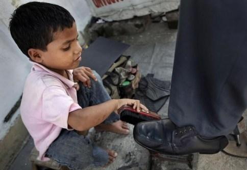 Seorang anak kecil di India bekerja sebagai tukang semir sepatu. foto via mief