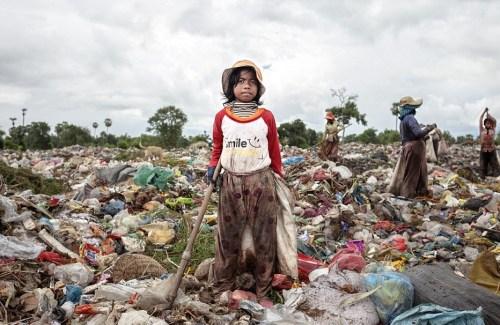 Seorang anak perempuan di Kamboja mengumpulkan sampah bekas. Foto via dailymail