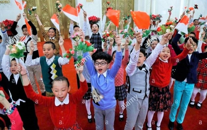 Chinese children with flowers and flags of China and Indonesia practice their cheering before a welcome ceremony for Indonesian/Foto: Dok. Stock