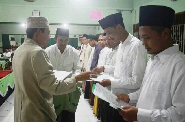 Ketua IKSAB TBS Nor Said MA. M.Ag. menyematkan tanda pengenal sebagai relawan Pasti TBS. Foto Dok. Pribadi