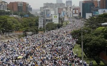 Ribuan demonstran anti-pemerintah berbaris di sepanjang jalan raya di Caracas, Venezuela, menentang Presiden Nicolas Maduro. (Foto: Ariana Cubillos /AP)