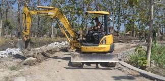 Alat berat eskavator atau bego dari DPU Kabupaten Ngawi dikerahkan dalam pelaksanaan TMMD ke-100 Kodim 0805/Ngawi. Foto Wahyu/ Rantelino