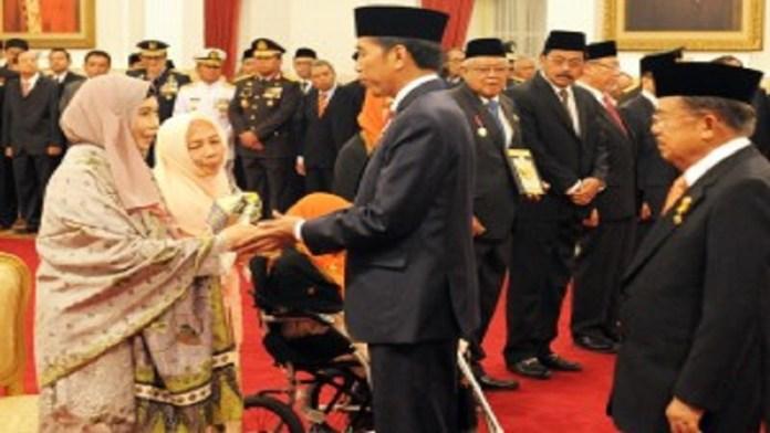 Presiden Jokowi diikuti Wakil Presiden Jusuf Kalla memberikan ucapan selamat kepada ahli waris penerima anugerak gelar Pahlawan Nasional, di Istana Negara, Jakarta, Kamis (9/11) siang. (Foto: Rahmat/Humas)