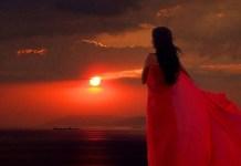 Perempuan bergaun merah memandang senja (Ilustrasi). Foto: Dok. hitvknew.ru