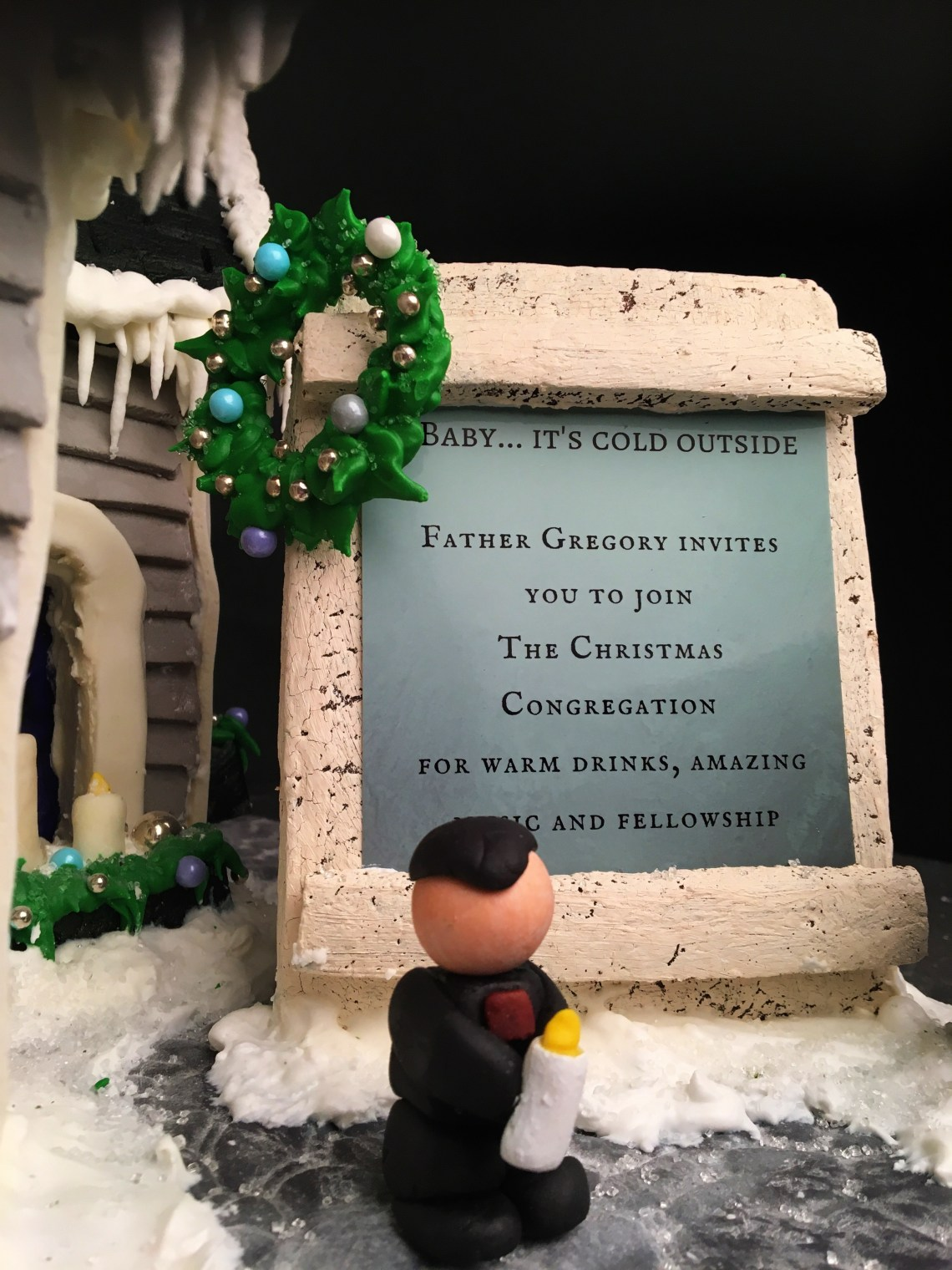 Father Gregory standing outside of the Christmas Congregation gingerbread church on Nutmeg Disrupted for the Festival of Trees in Edmonton in 2017