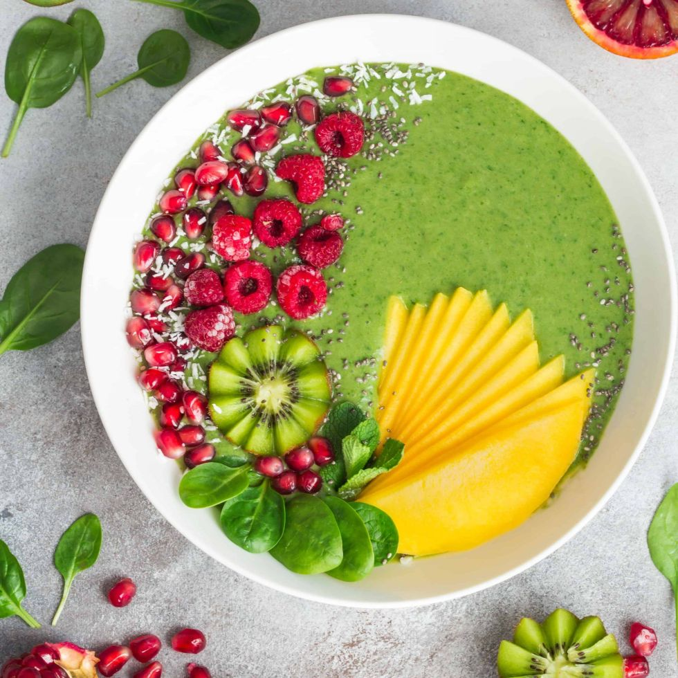 Fresh green healthy smoothie bowl with fruits and berries