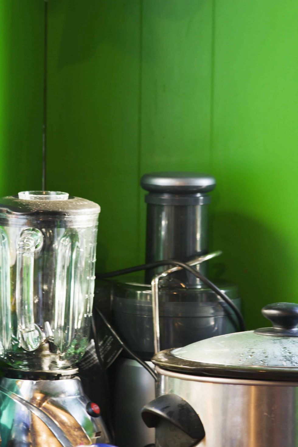Blender and juicer with green background
