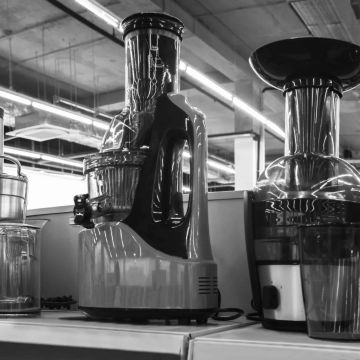 Black and white image of different types of juicers on a store shelf