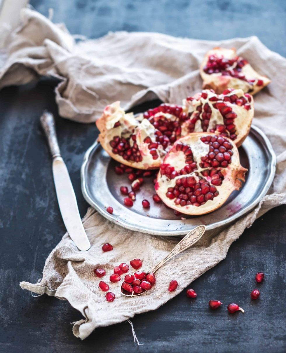 Red ripe peeled pomegranate on rustic metal plate and beige kitchen towel over dark background.