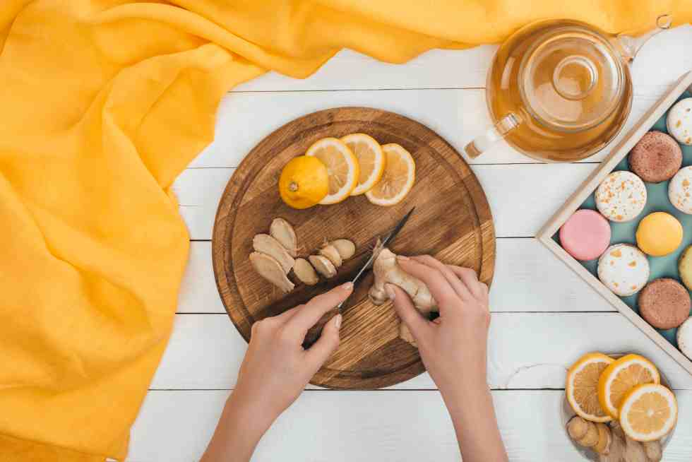 woman cutting ginger and lemons on cutting board