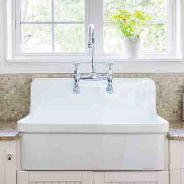 Large white porcelain kitchen sink and granite stone countertop under window