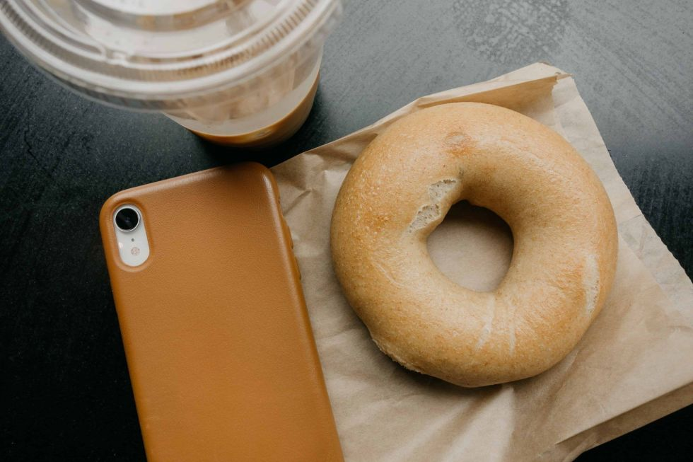 Bagel next to coffee and phone