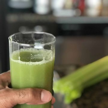 Man holding a glass of celery juice with celery sitting on a kitchen countertop in the background