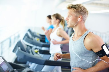 A young man jogs on a treadmill with a group of fellow gym members