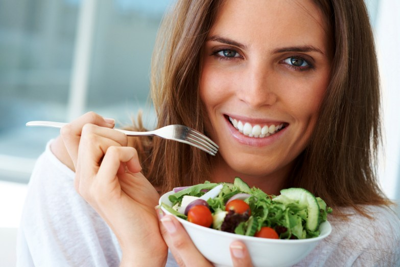 Close-up of happy woman eating vegetable salad