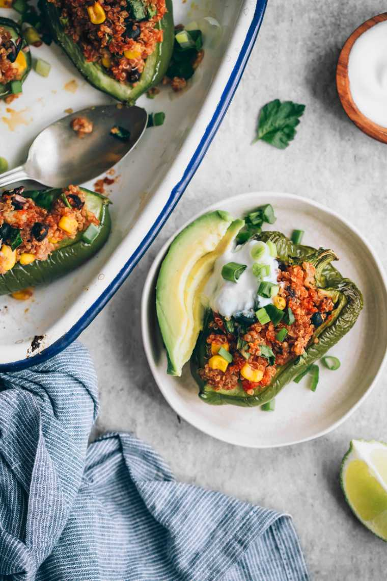 one gluten-free stuffed pepper with avocado on a plate next to a baking dish
