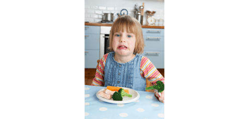 This image shows a girl that is unhappy and fussy about her food