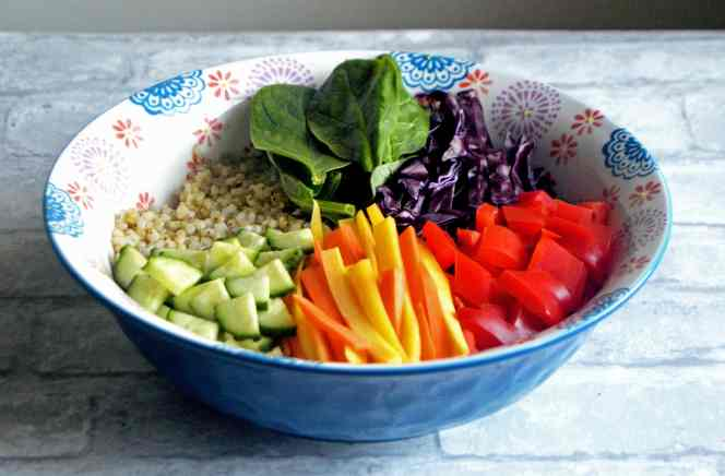 A vegan & gluten-free grain bowl topped with rainbow veggies