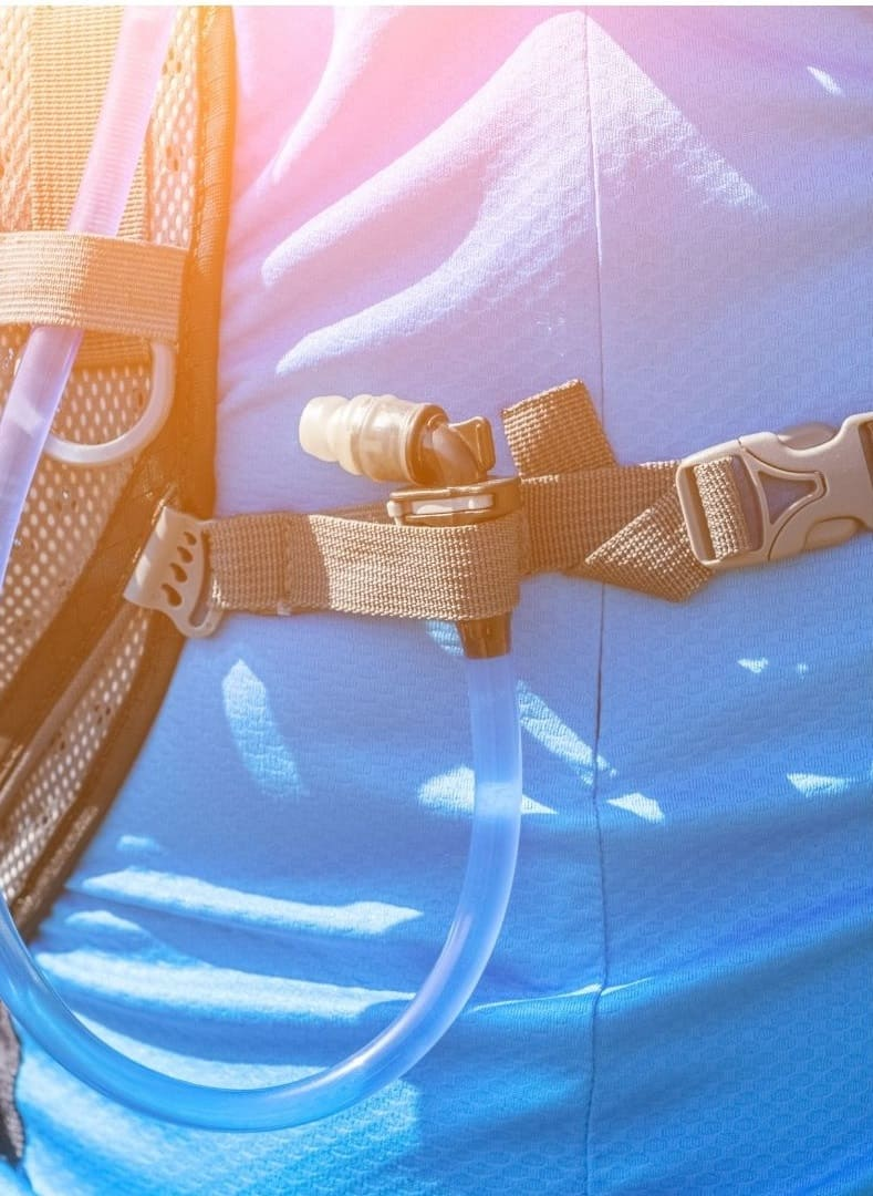 closeup of running hydration pack on man with blue shirt