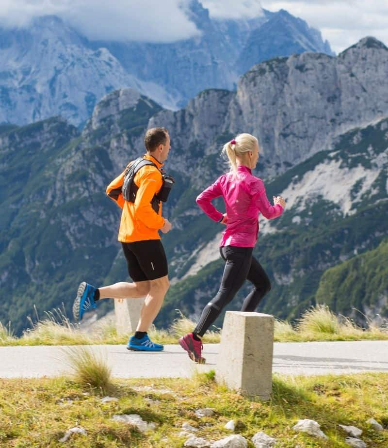 woman and man running on trail with mountains in the background