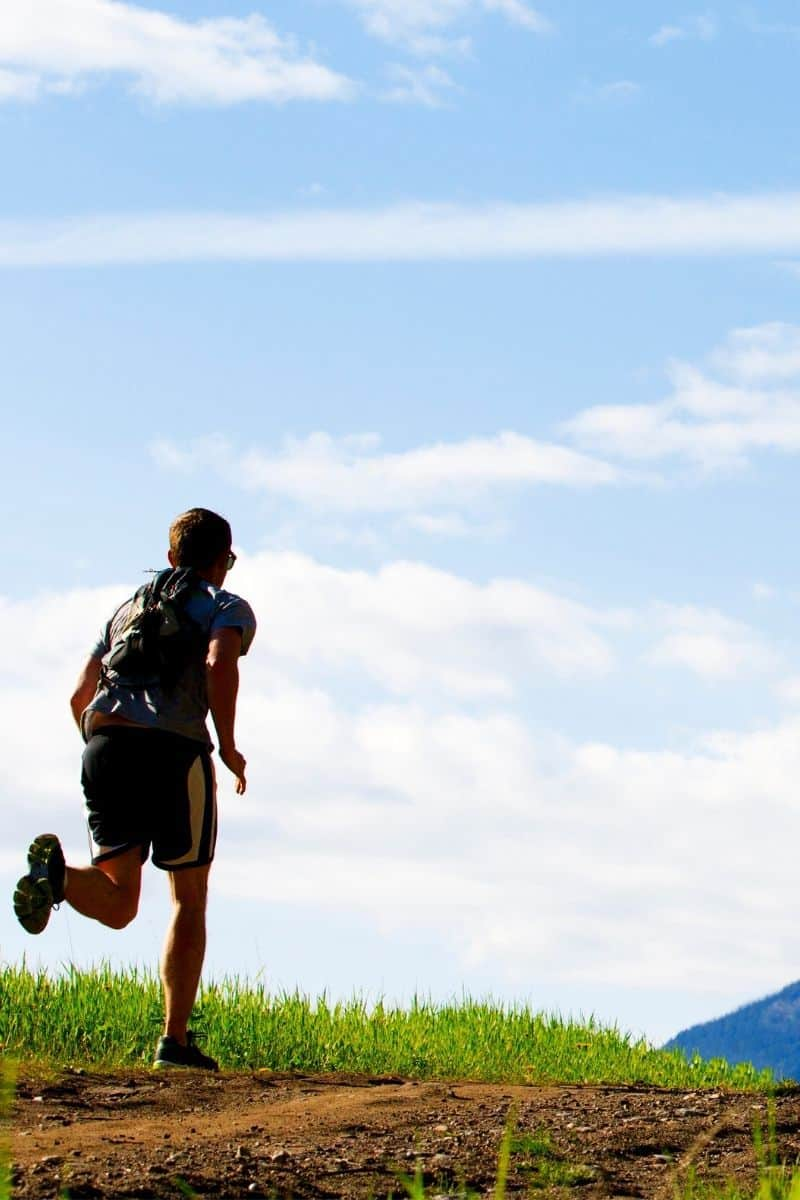 male running towards mountains with backpack