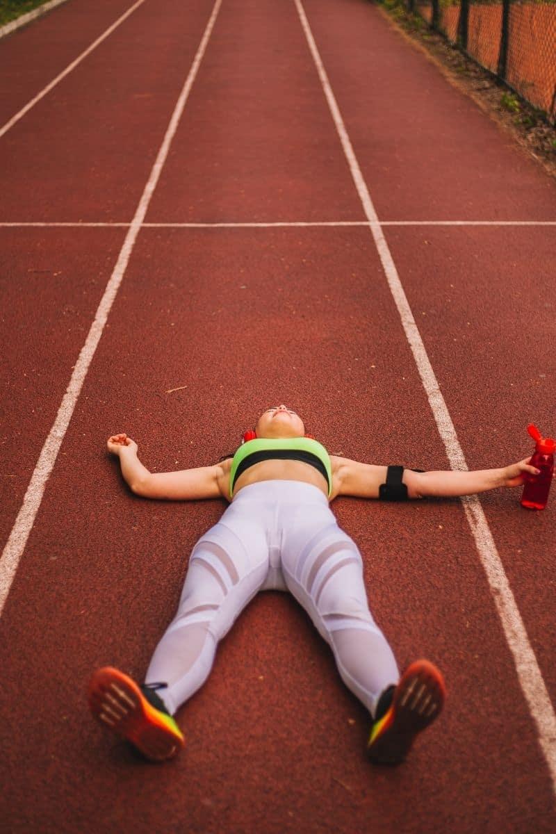 runner lying down on track