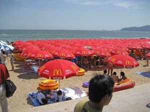 Chinese beach scene with McDonald's shade umbrellas covering the beach