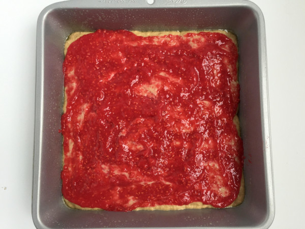 Raspberry puree spread over first layer of batter