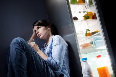 Woman by fridge, midnight snack concept