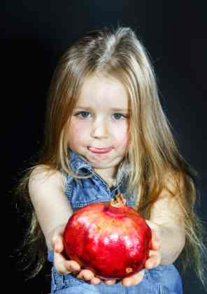 Little girl posing with pomegranate