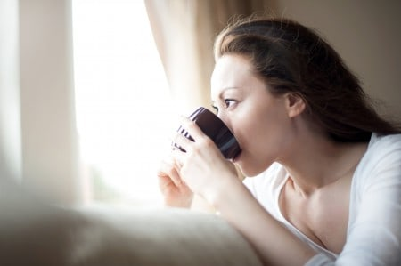 Girl drinking coffee by a window
