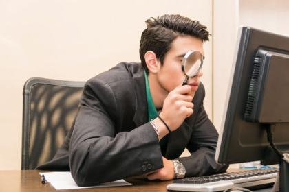 Man at computer with magnifying glass