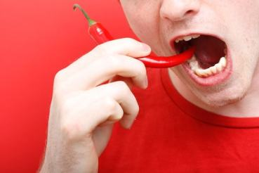 A man eating chili pepper