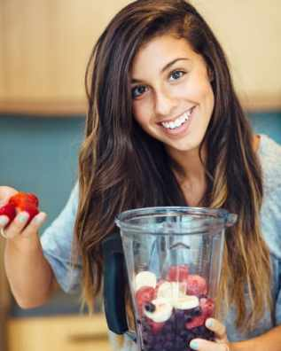 Girl putting frozen fruit in a blender