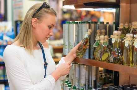 Young woman choosing olive oil in grocery store.
