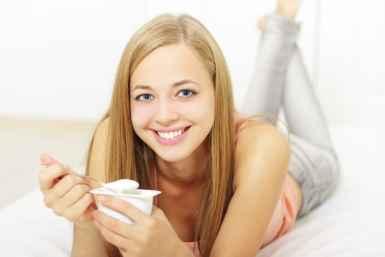 Attractive girl eating yogurt