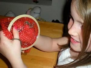 child stitching needlepoint on mesh bag