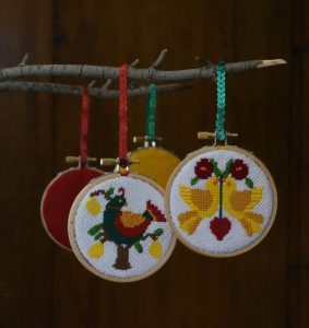 12 Days needlepoint ornaments finished in wood embroidery hoops