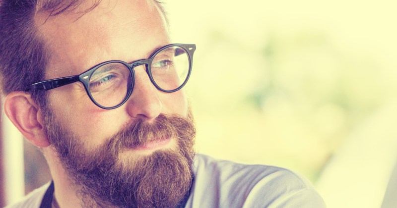 Mid-30s man with glasses looking away