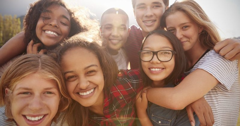 Group of young teenagers hugging and hanging out